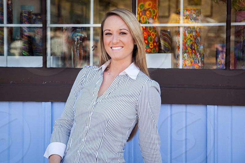 woman standing in front of shop window smiling photo