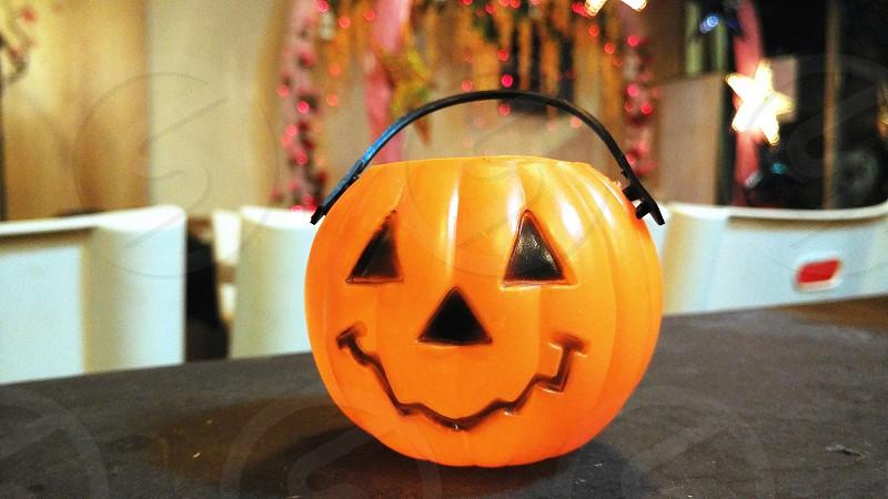 plastic pumpkin candy bag on black table photo