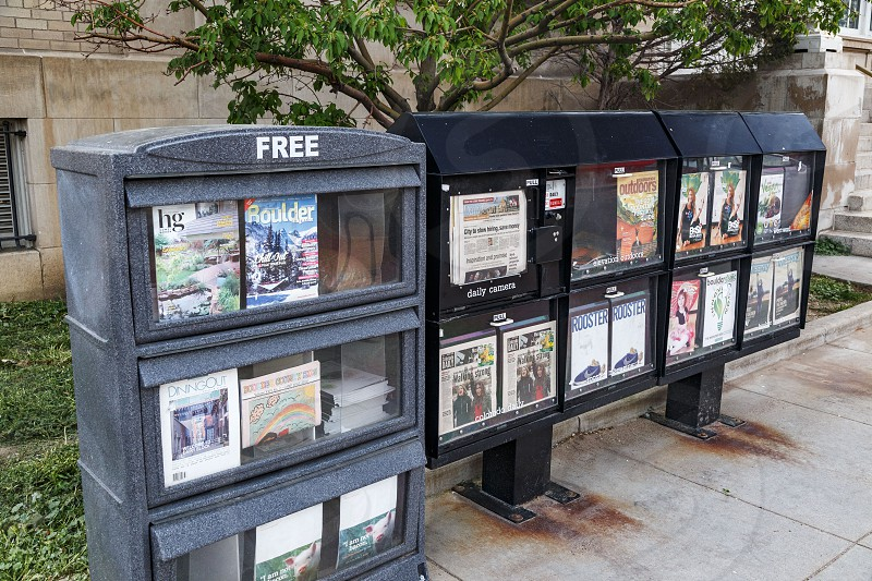 Newsstands along sidewalk with free and paid print publications in Boulder Colorado photo