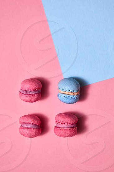 Homemade appetizing macaroons with reflection of shadows on a blue pink background. Top view photo