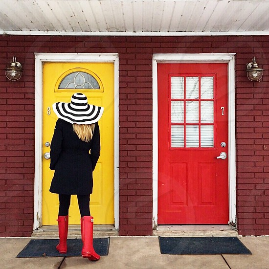woman in black coat and red hunter galoshes standing in front of yellow painted wooden door photo