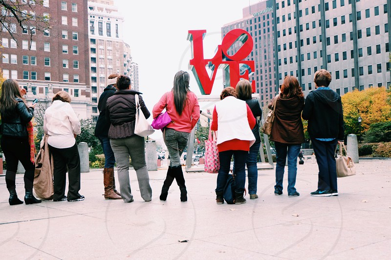 group of people standing in front of a love sign photo