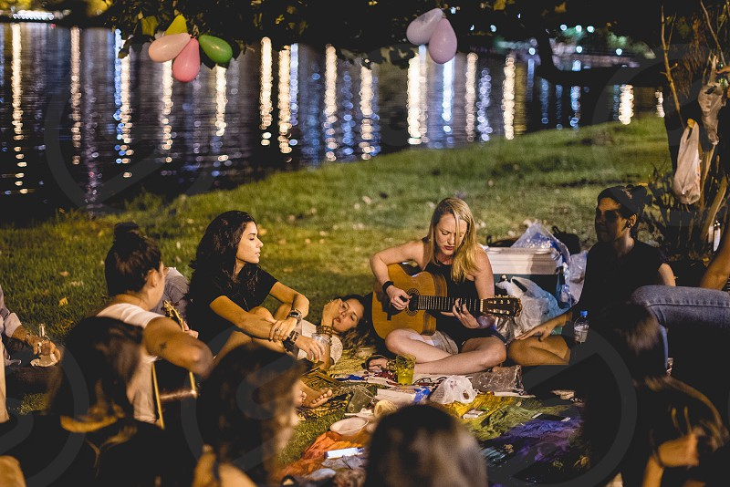 Friends having fun at the park playing guitar  photo