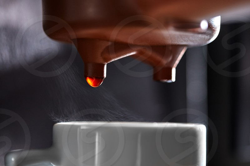 Macro photo of dripping coffee in a coffee machine dripping into a cup. The process of making a drink photo