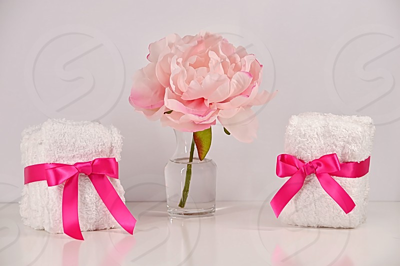 Two bundles of small towels wrapped with pink ribbon a clear vase and pink peony flower. photo