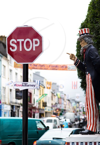 red stop sign in front of uncle sam statue at sidewalk photo