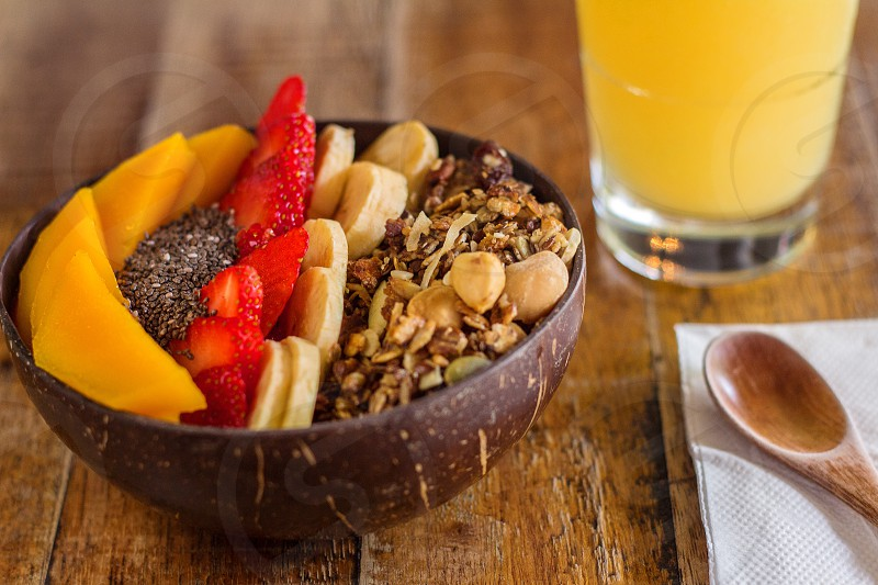 smoothie bowl for healthy breakfast. peach strawberry banana toasted muesli and chia seeds with berry base smoothie served on a wooden table with wooden soon and orange juice photo