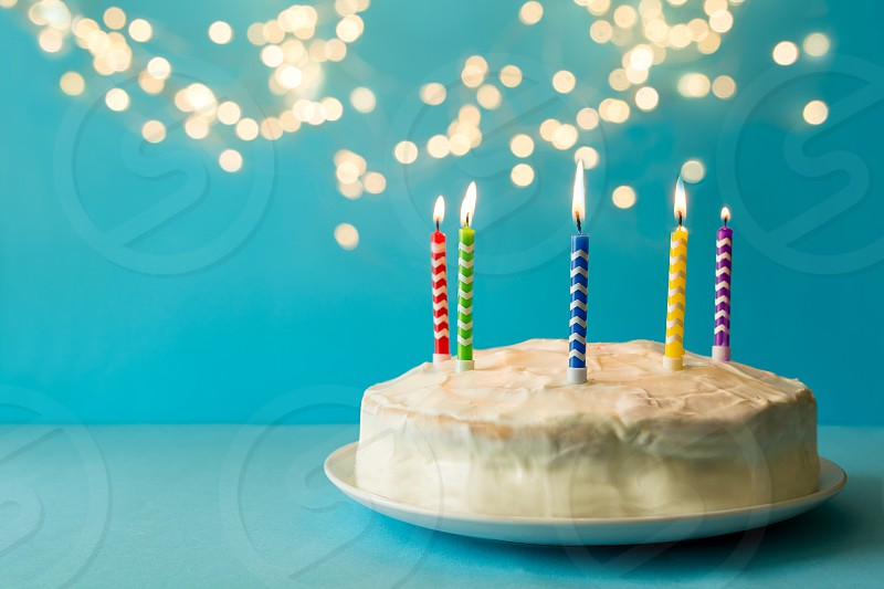 White birthday cake with colorful candles on blue background against defocused light. Holiday celebration concept. Copy space photo