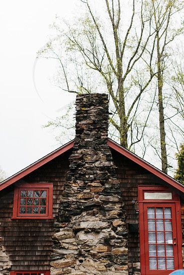 brown and red cabin with stoner chimney under white sky during daytime photo