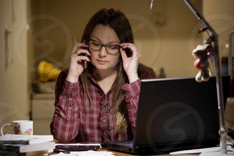 Woman in home office doing work on laptop and talking on phone photo