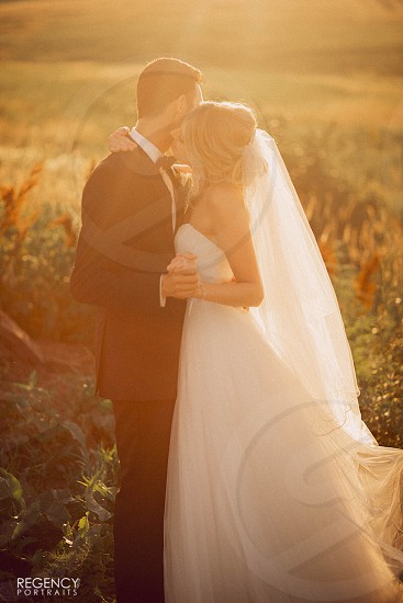 Fog haze sun sunlight lens flare flare sunset warmth summer golden golden light light couple love bride groom bride and groom married marriage wedding wedding day white dress black tux black tuxedo tuxedo bow tie veil dancing holding hands I do field Nebraska  photo
