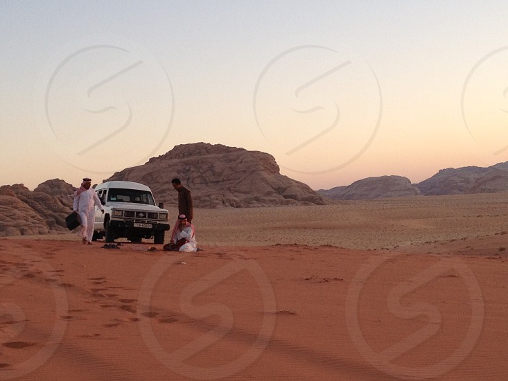 men in white thawb and red and white keffiyeh outside white truck in orange desert sand at sunrise with rocky hills in distance photo