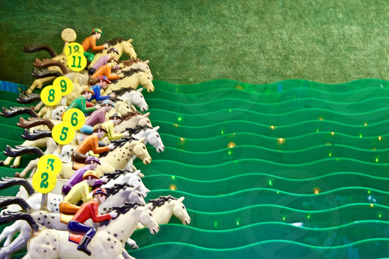 Horse racing carnival game with plastic horses lined up ready for the race to begin along green plastic track photo
