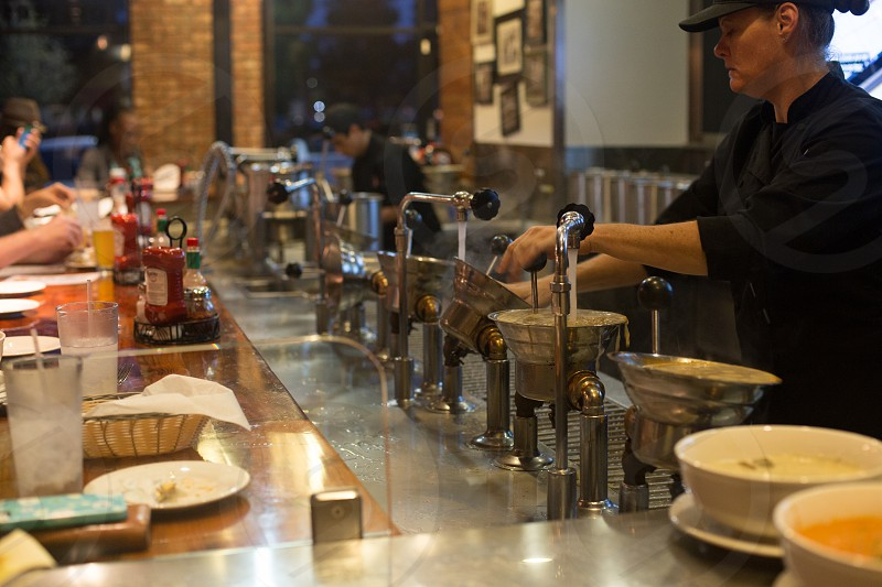 woman in black using stainless steel tools at restaurant photo