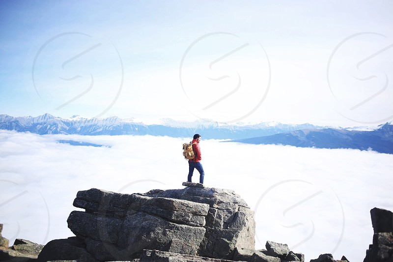 man in red jacket standing on rock by the mountain top leveled with white clouds photo