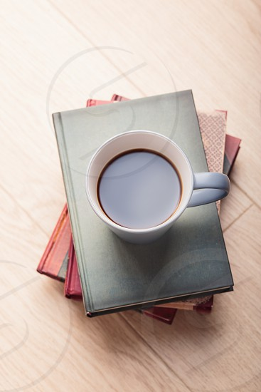 A few books with cup of coffee on wooden floor photo