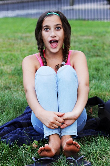 Brown Haired Girl Wearing Blue Jeans and Pink Shirt Sitting on Grass photo