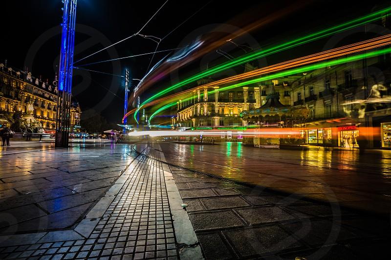 Tram moving through Place de la Comédie Montpellier France. Long exposure light trails photo