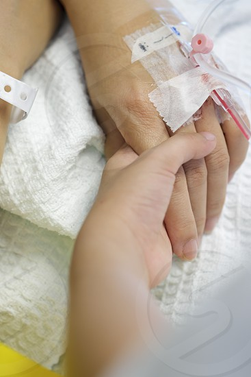 Close-up of kid holding the hand of a woman patient with IV drip at the hospital  photo