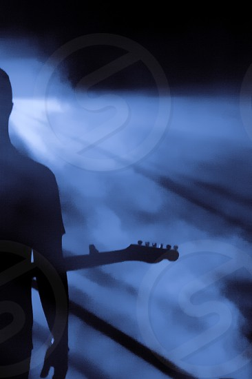The shape of a guitarist on foggy stage photo