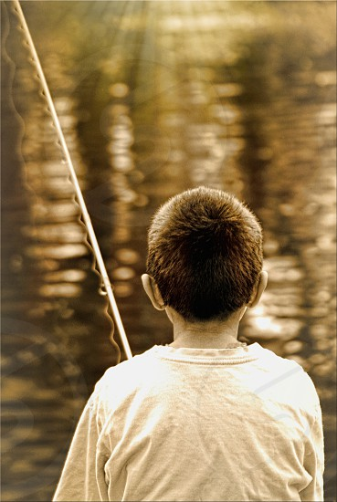 Sepia image of a boy fishing seen from behind. photo