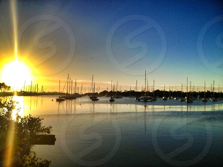 silhouette of fishing boats on body of water at golden hour photo