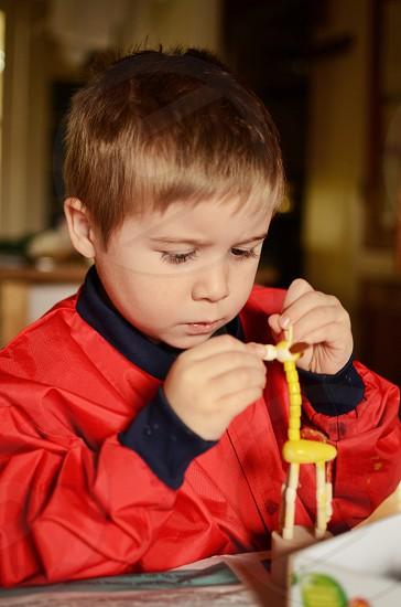 Jack painting his toy giraffe 2. photo