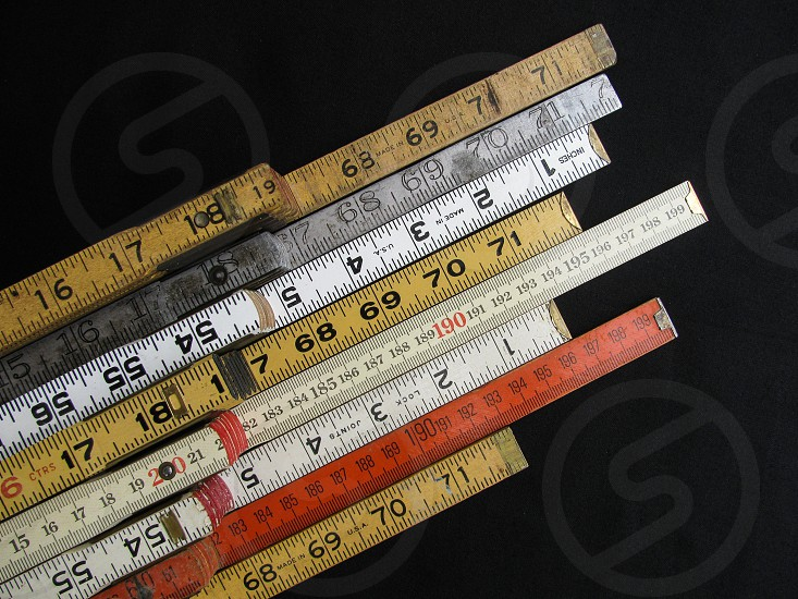 Collection of old folding rulers and scales in metric and inch measurement represent concepts of accuracy craftsmanship and precision. photo