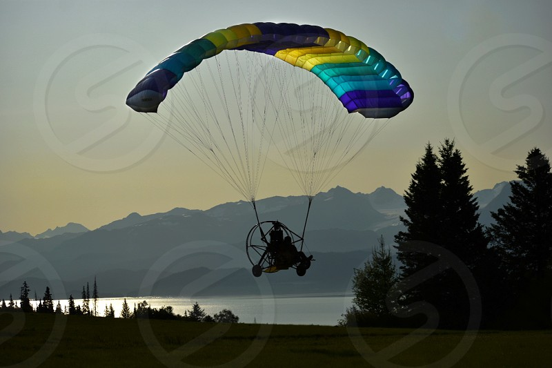 Silouette of a man flying a powered parachute over the meadows toward the ocean and mountains. photo