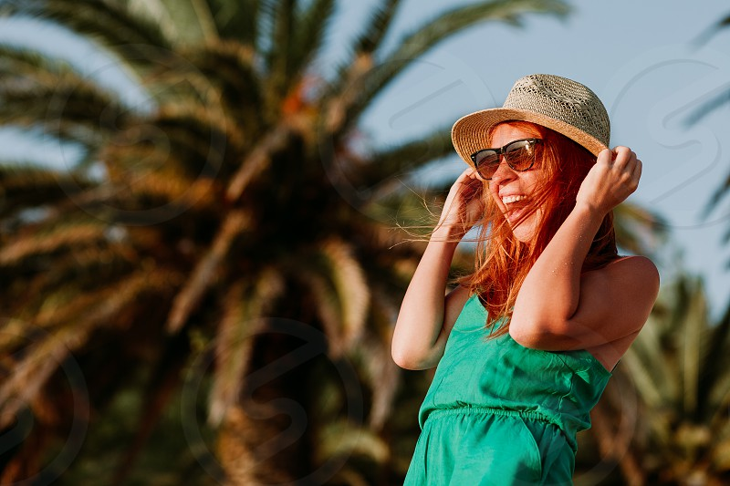 Young woman having fun on the wind by the palm trees photo