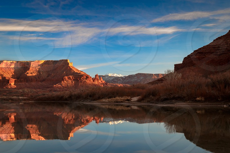 Snow capped La Sal Mountains and Fisher Towers reflect in Colorado River near Moab Utah photo