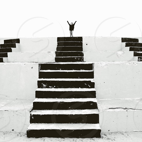 woman in black standing on top of black and white concrete stairway photo
