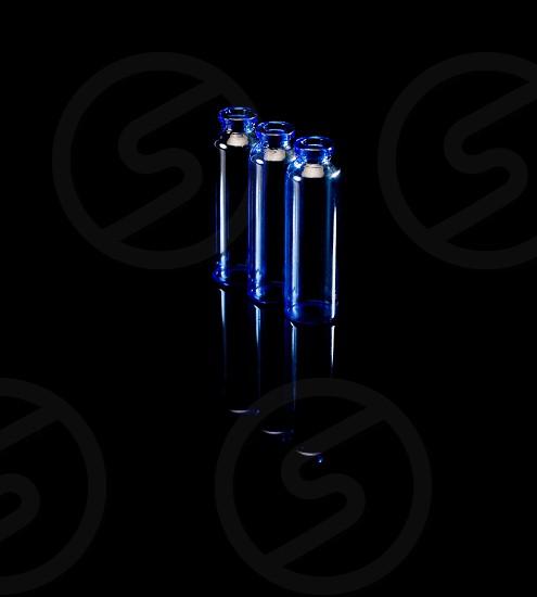 blue glass vials over black background backlit photo