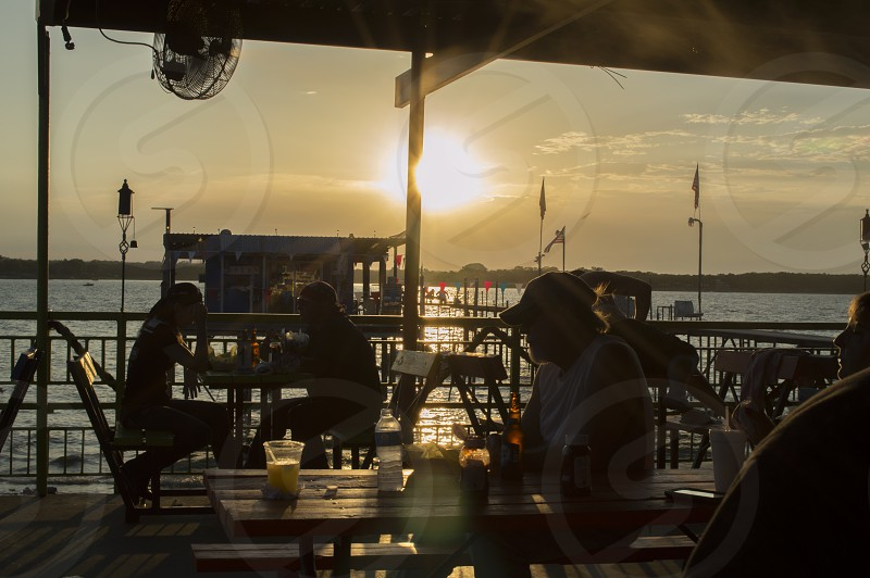 Silhouette of people dining at a lakeside restaurant as the sun sets on the lake behind them casting a soft golden glow on the scene. photo