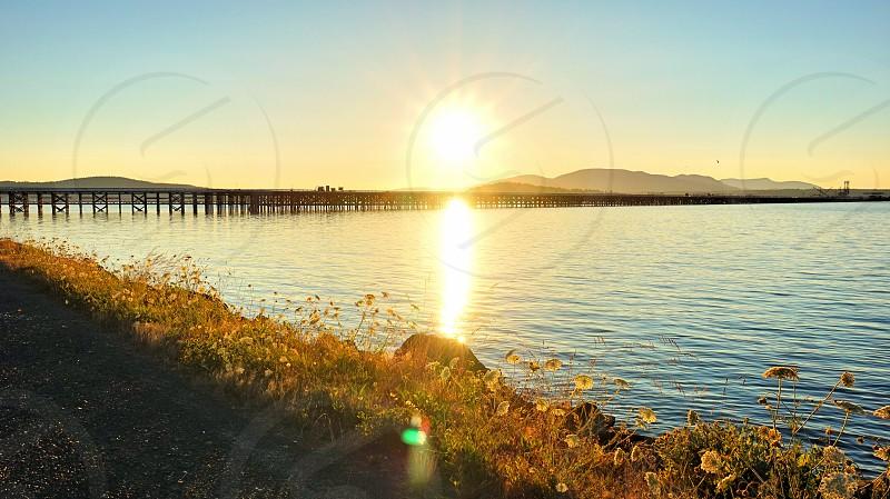 sunrise over bridge over water photo