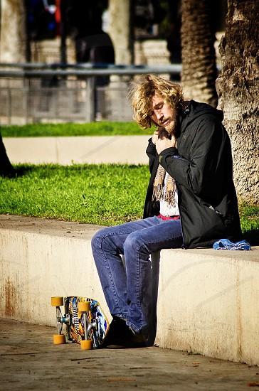 man wearing black jacket with hood and skateboard photo
