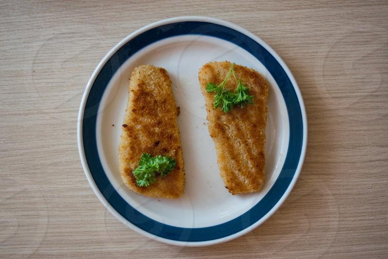 Top view of roasted fish fillet pieces in breading on white plate with parsley topping photo