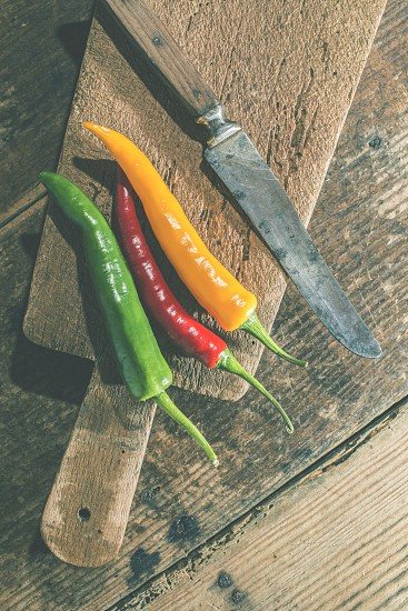 Hot peppers on wooden kitchen cutting board photo