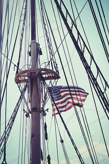 ship's mast with u.s.a. flag below bright sky during daytime photo