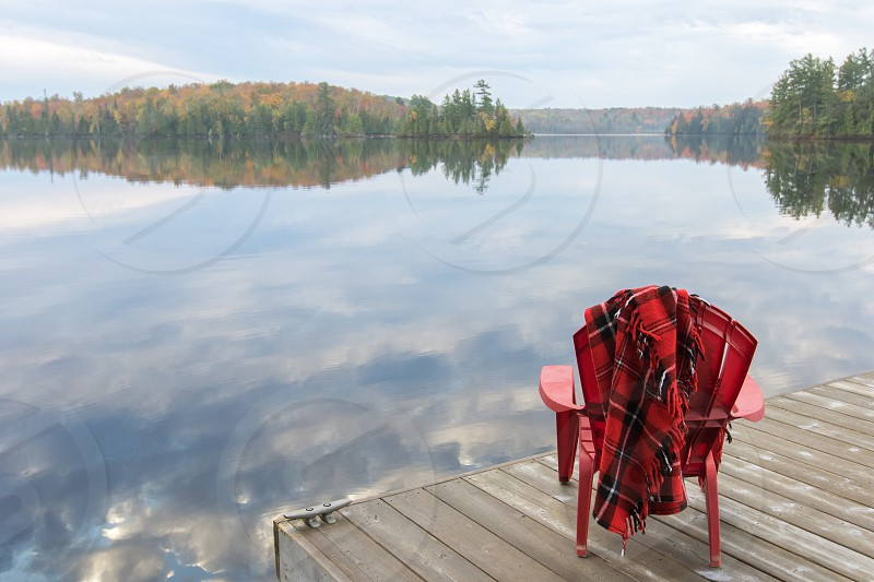 A red adirondack chair with a plaid wool blanket on a dock overlooking a lake with fall color photo