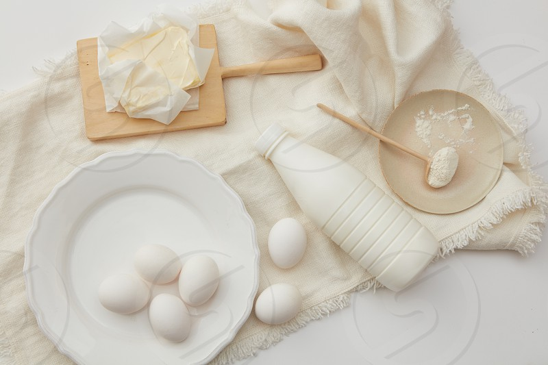 Eggs milk flour and butter to bake a cake on a white napkin  flat lay photo