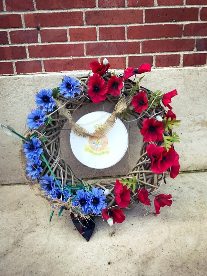 Outdoor day vertical portrait colour Thiepval France Somme western front Battle site battleground historic historical red poppy flowers remembrance commemoration monument respect stone WWI WW1 World War One First World War Memorial carved carving masonry  country crucifix cross blue Wreath flowers woven photo