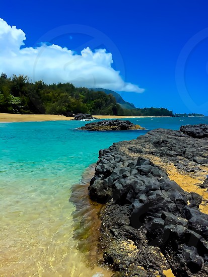 Tropical island beach scene lava rock turquoise ocean water blue sky photo
