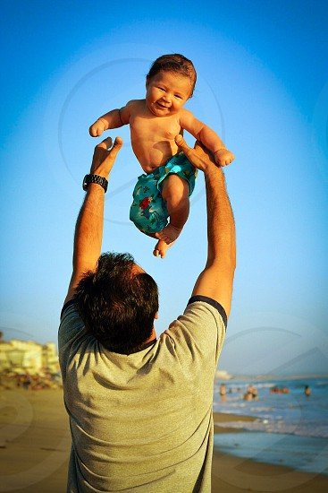 man in grey and black shirt lifting baby in blue short near sea under clear blue sky during daytime photo