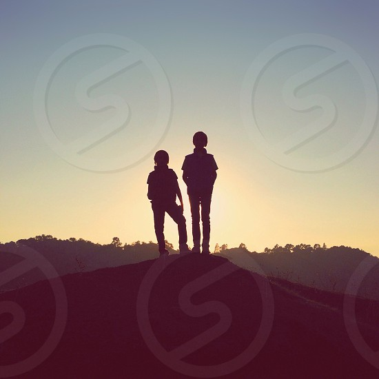 children standing in hill silhouette  photo