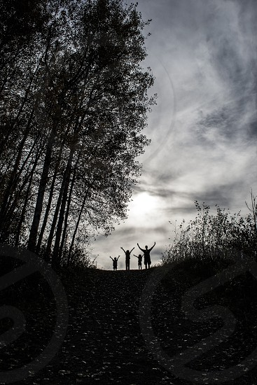 Silhouette of family at top of hill holding their hands up photo