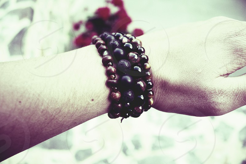 a arm with four bracelets in the color brown black and tigereye. A manly arm with a light background. photo