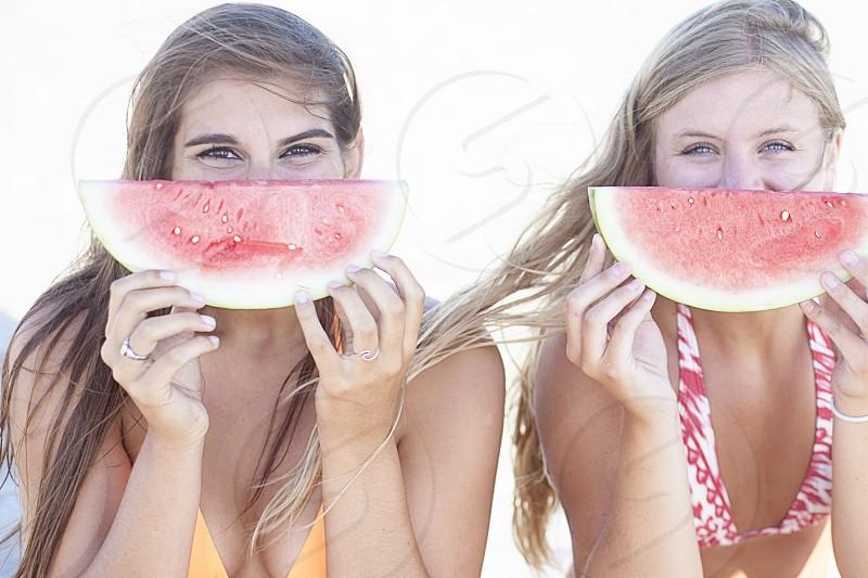 2 women eating watermelon photo