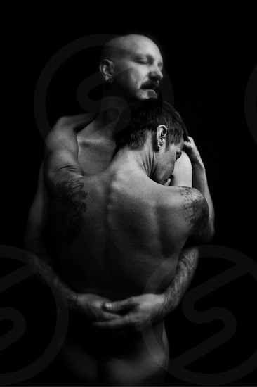 grayscale photography of naked man and woman hugging each other photo