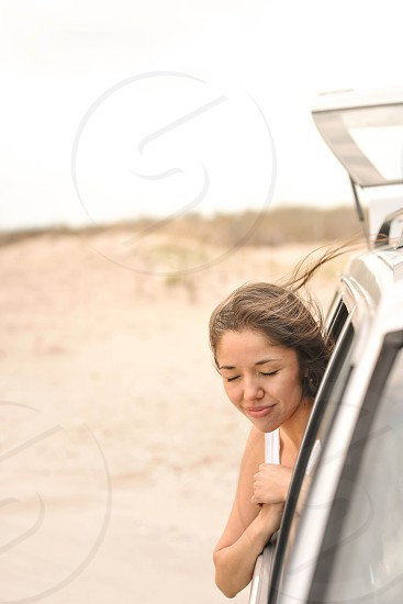 woman with head out of car window photo